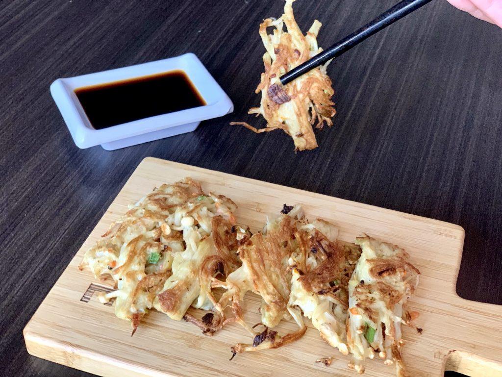 enoki mushroom being held with chopsticks