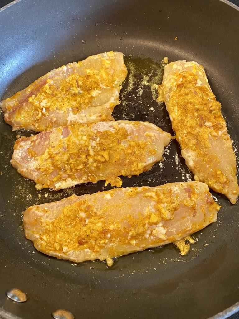 frying tilapia fillets in a pan