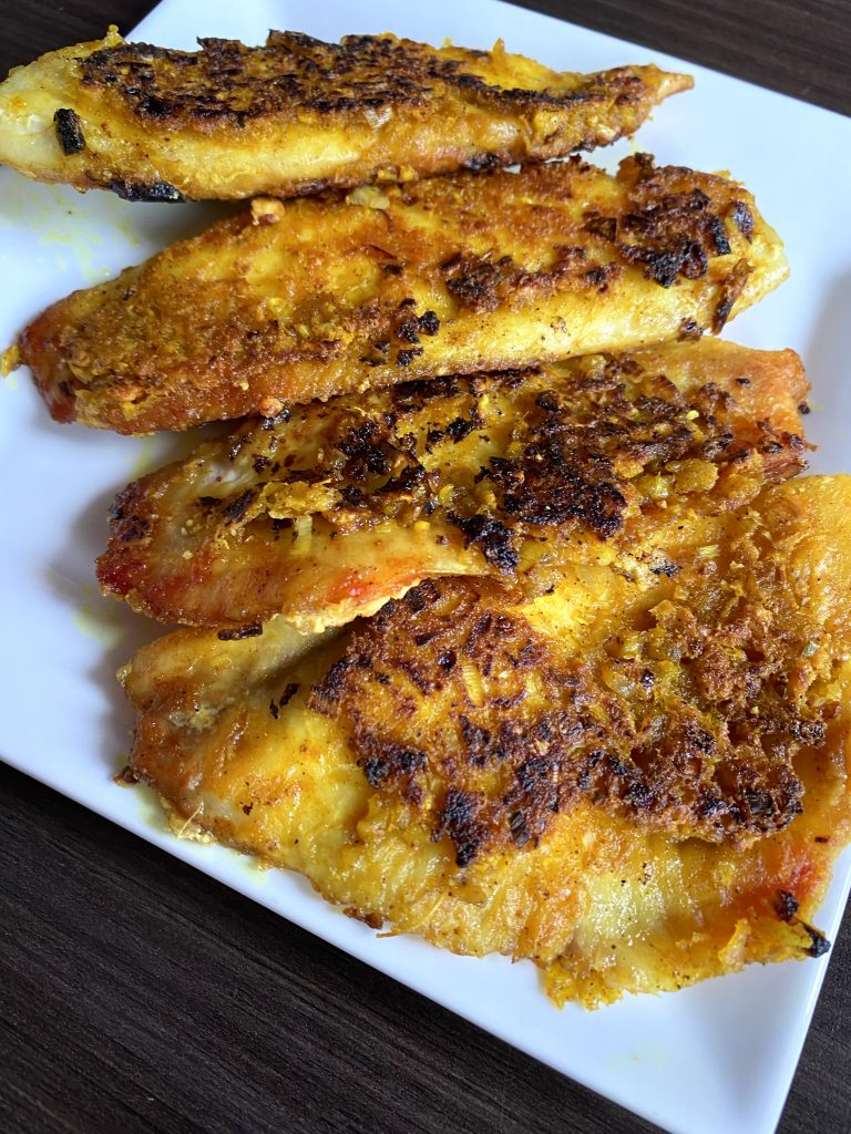 Vietnamese fried fish with lemongrass and turmeric on a square plate