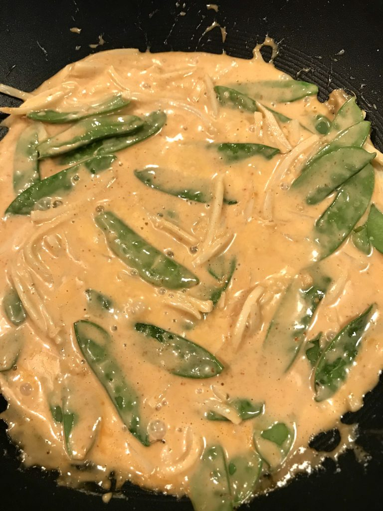 thai red curry simmering in a wok