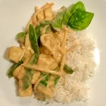 thai red curry with rice on a white plate