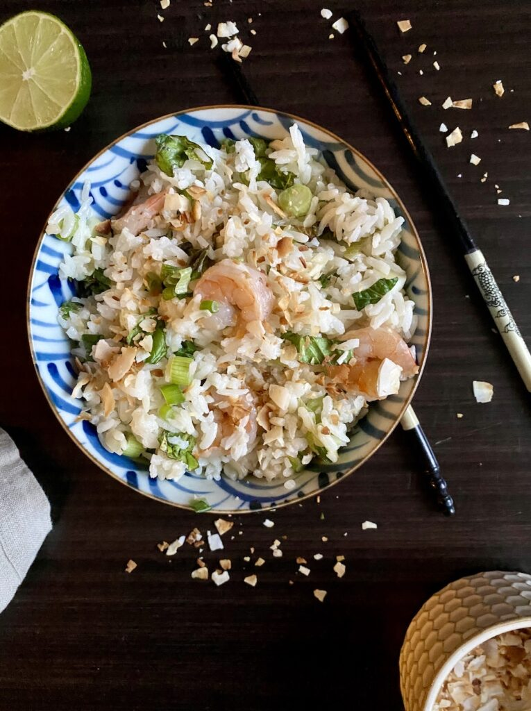 bowl of herbed rice with chopsticks and coconut flakes surrounding it