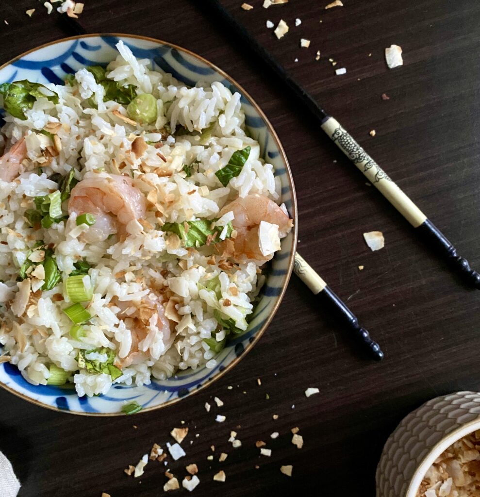 Nasi ulam in a bowl with chopsticks and coconut flakes around it