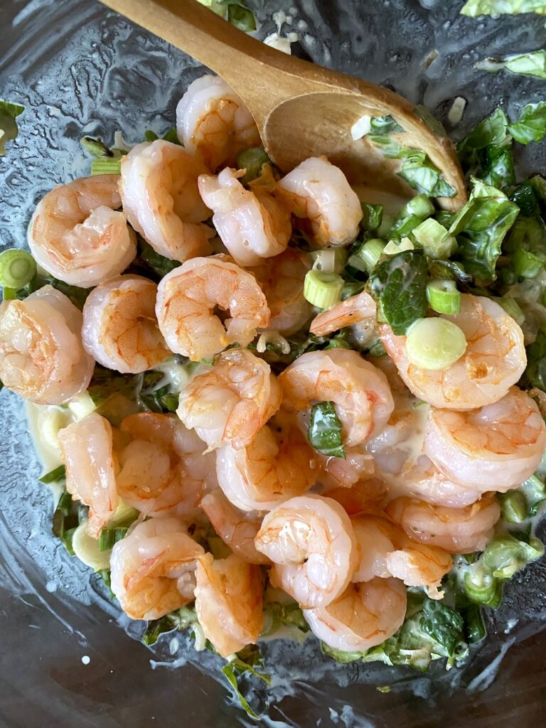 mixing herbs, coconut milk, scallions, and shrimp with a wooden spoon in a bowl