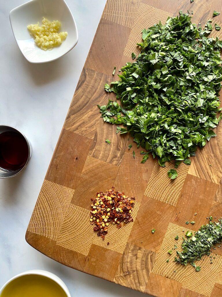 chopped parsley and oregano on a cutting board