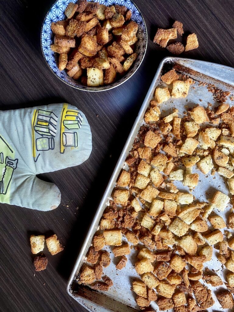 homemade croutons on baking tray and in bowl