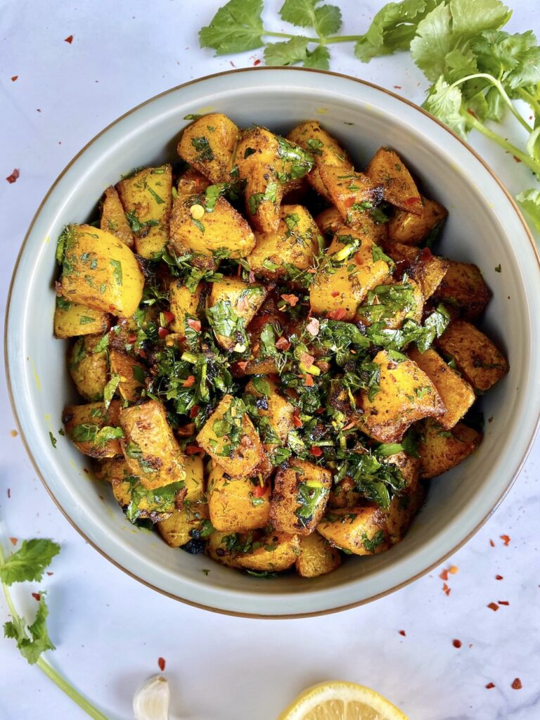 Batata Harra in a bowl with fresh herbs in the background