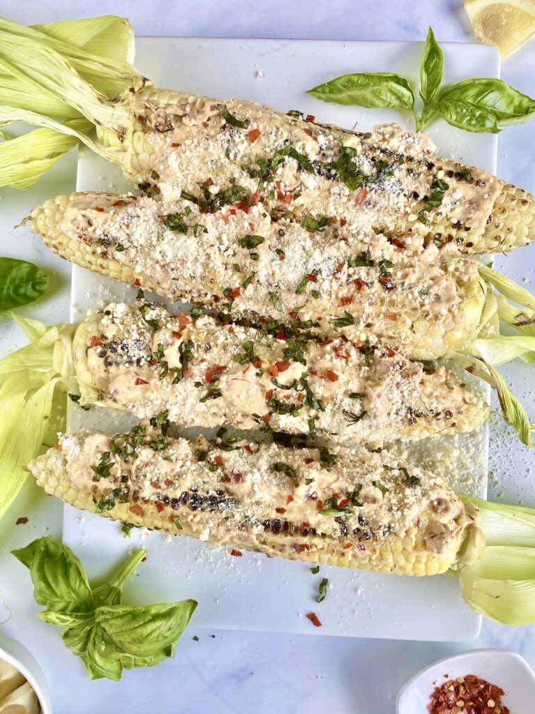 Italian street corn on a plate with basil and red pepper flakes
