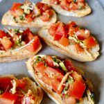 bruschetta crostinis with basil and parmesan on a platter
