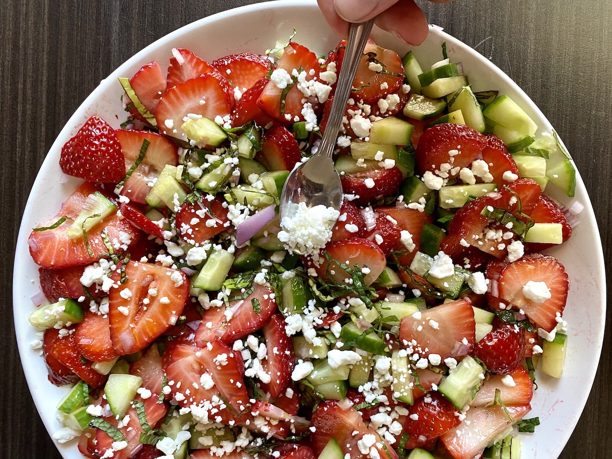 spooning goat cheese over strawberry salad
